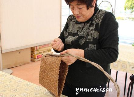 ツルを編んでカゴに縫い付けます。