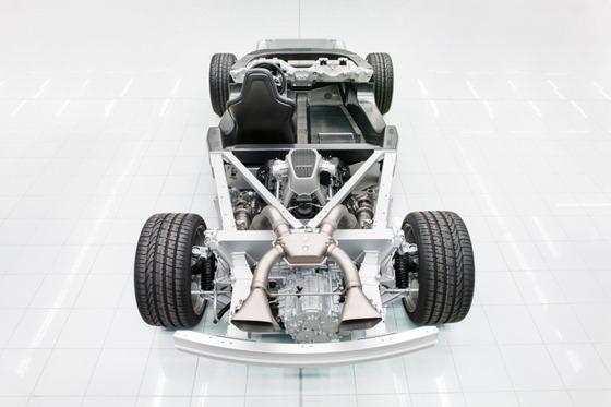 マクラーレン・スーパーカー・ファクトリー:車の中心部の黒いカーボンファイバー製モノセルがむき出しになったプロトタイプ・シャシー。三角形の中心にはエンジン。加熱を改善するためシャシーの低い位置に取りつけられる。