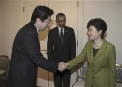 日米韓3カ国首脳会談を前に、安倍晋三首相と握手する韓国の朴槿恵大統領(右)。中央はバラク・オバマ米大統領。=3月25日、オランダ・ハーグ(AP)
