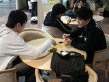 バス待ちの時間を利用してカードゲームに興じる学生達