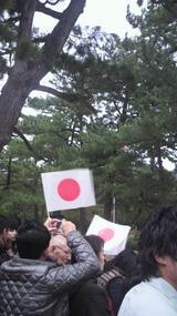旗を持って待つ人々。
