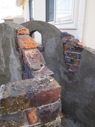 朽ちた壁から崩れ出るレンガ