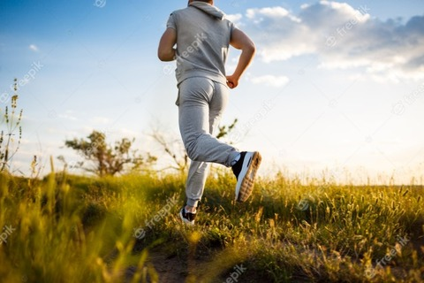 close-up-of-sportive-man-jogging-in-field-at-sunrise_176420-5186