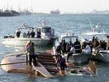 バーレーンのムハラクで31日、転覆した遊覧船を海岸近くに引航して捜索にあたる人たち=AP
