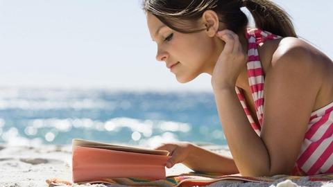 ビーチで読書する女性