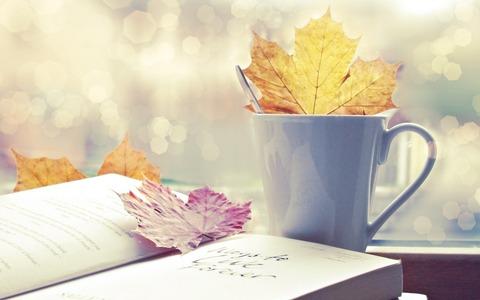 カップと落ち葉と本