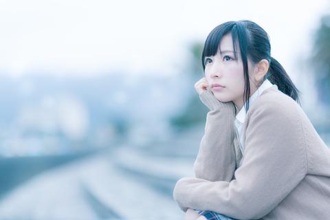 もの寂しげな表情で考えこむ女子高生