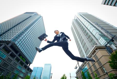ビジネスバックを持ち大きく飛ぶ会社員