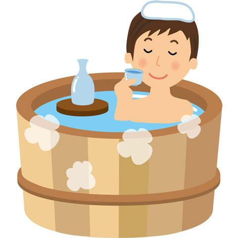 温泉に入って日本酒を飲む男性