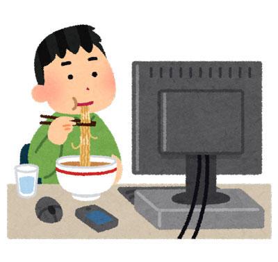PCデスクの上で食事をしている男性