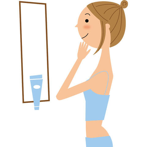 鏡を見ながら肌の状態を確認する女性