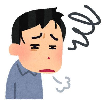 疲れきった表情で溜息をつく男性