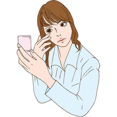 鏡を見ながら目元を触る女性