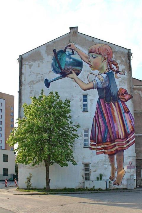 小さな木に水をあげる少女