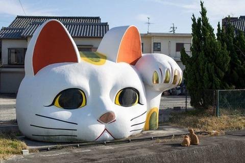 巨大な招き猫とネコ2匹