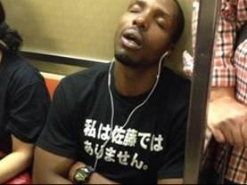 地下鉄乗車の黒人のTシャツが私は佐藤ではありませんって意味不明の爆笑画像