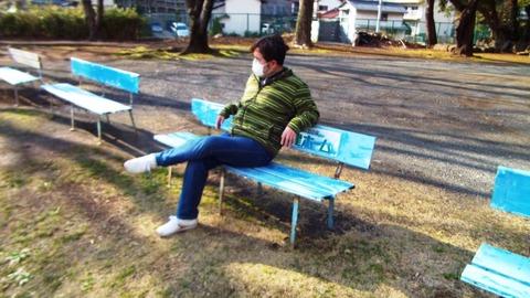 1月日曜の昼下がりに公園ベンチに座る僕の写真