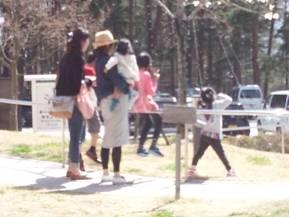 おぶちさわ道の駅の外部テラス前の野原で家族の女の子たちが陽を浴びて舞い上がりそうな光景を写真を撮影