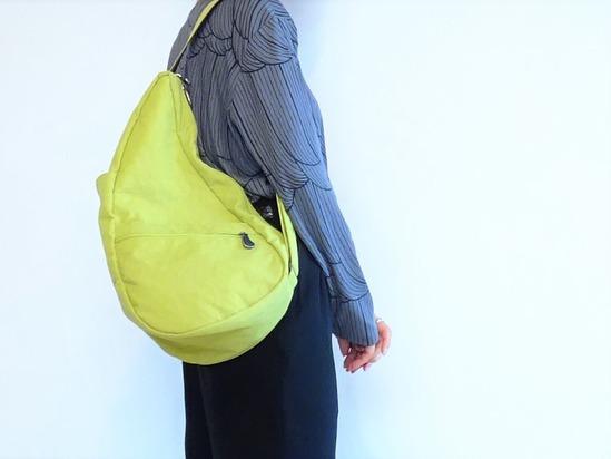 濃いグレーのカットソーと黒いパンツにピスタチオカラーのバッグ (3)