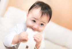新しいスマートフォンを食べる赤ちゃん [モデル:Lisa]