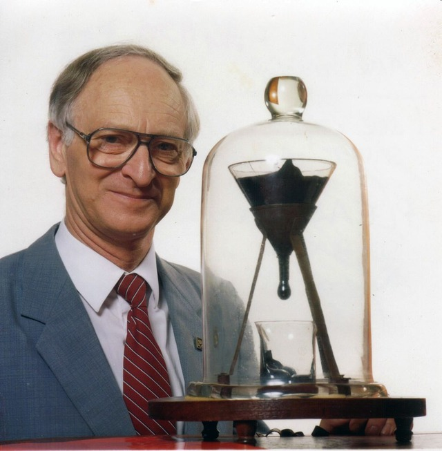 1024px-Pitch_drop_experiment_with_John_Mainstone