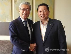 握手を交わす金会長(右)と竹田会長