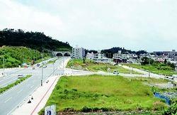 32軍司令部壕跡などがあった高津嘉山(左のトンネル部分)と旧軍施設壕群が埋まっていた区画整理地区(手前の交差点周辺)