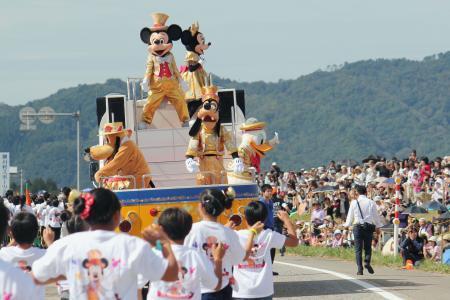 農村でディズニーパレードに参加するミッキーマウスと仲間達