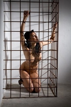 9200815-beautiful-nude-girl-locked-in-cage-in-dark-dungeon-style
