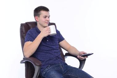 ソファに座りコーヒーを飲んでくつろく男性
