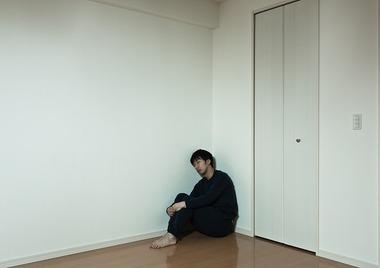 部屋の隅で体育座りする男性