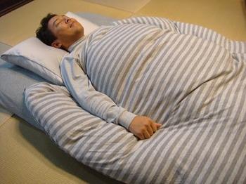 布団で寝る男性