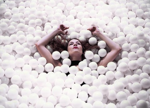 woman-floating-with-arms-raised-in-ball-pit