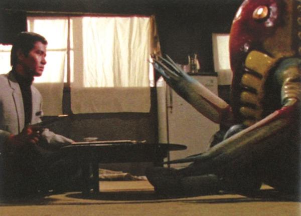 ちゃぶ台を挟んで座るモロボシ・ダンとメトロン星人