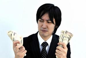 お金を握り締める男性