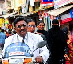 バンガロールの街中でバイクに乗る記者二人