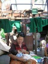 ビルマの現状、屋根の無い家の中で乳飲み子を抱く母