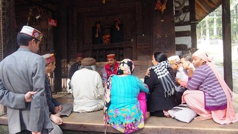 寺院外で祈祷師の話を聞く人