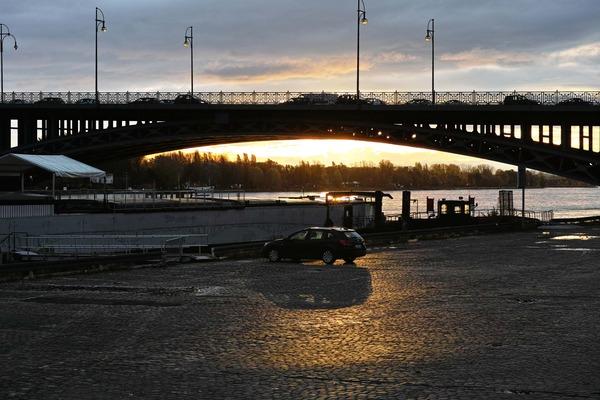 橋にかかる朝日と車
