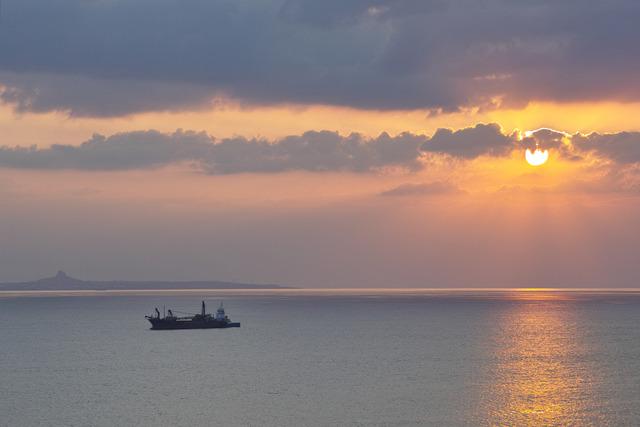 船と夕日と伊江島タッチュー