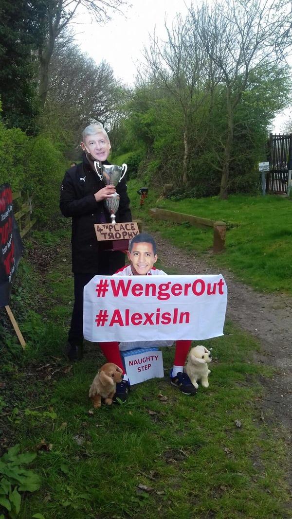 【画像】アーセナル「Wenger Out」派サポが顔写真被り「4位トロフィー」を掲げて抗議www