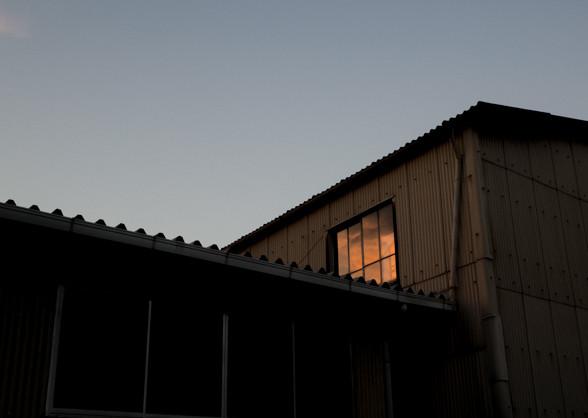 近くの工場の窓に映った夕日