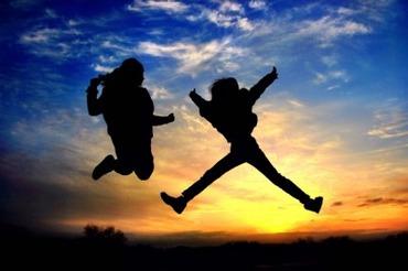 未来への希望を持ち、夕日に向かってジャンプする二人