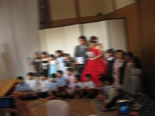 赤いドレスと幼稚園の子供達
