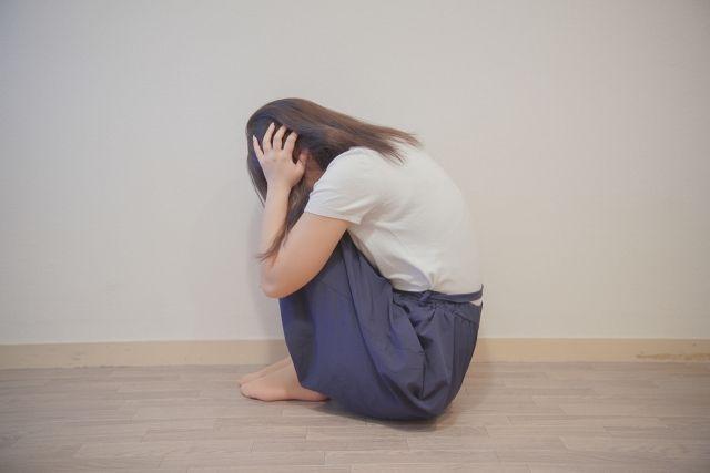 頭を押さえ膝を抱え込んで泣く女性