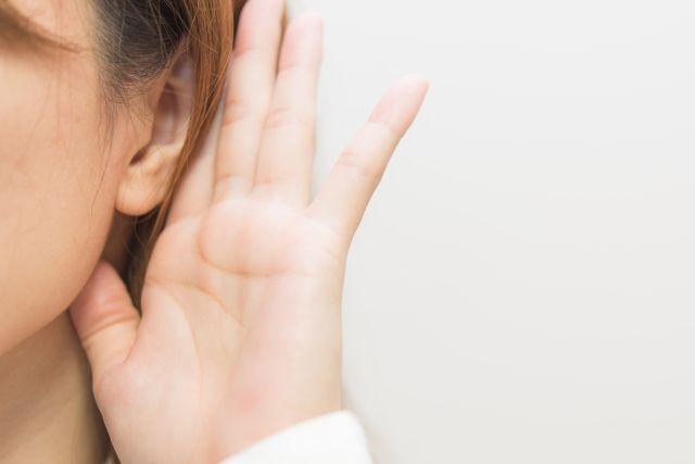 情報を聞くために耳に手をあてる女性