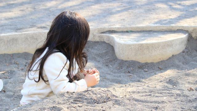 砂場で遊ぶ未就学児の女子児童