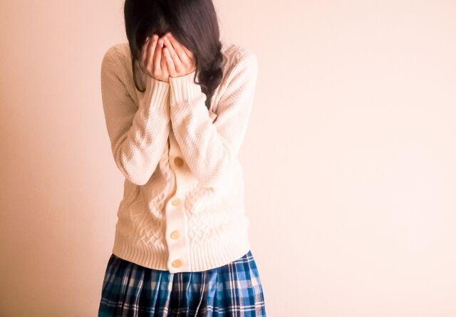 顔を覆って泣く女学生
