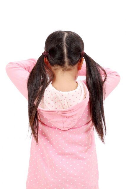 後ろを向いて泣くツインテールの小学生の女の子