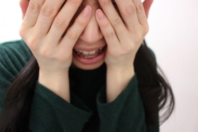 目を隠して口を開けて泣く女性